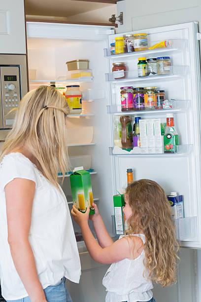 Mère et fille tenant des jus de fruits devant un réfrigérateur - Photo