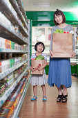 istock Mother and daughter holding grocery bags in supermarket, Beijing 185654841