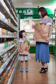 istock Mother and daughter holding grocery bags in supermarket, Beijing 186324824
