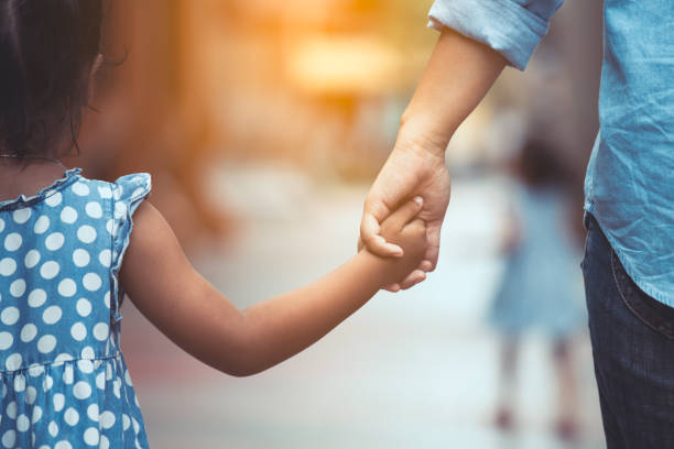 Mother and daughter holding hand together in vintage color tone stock photo