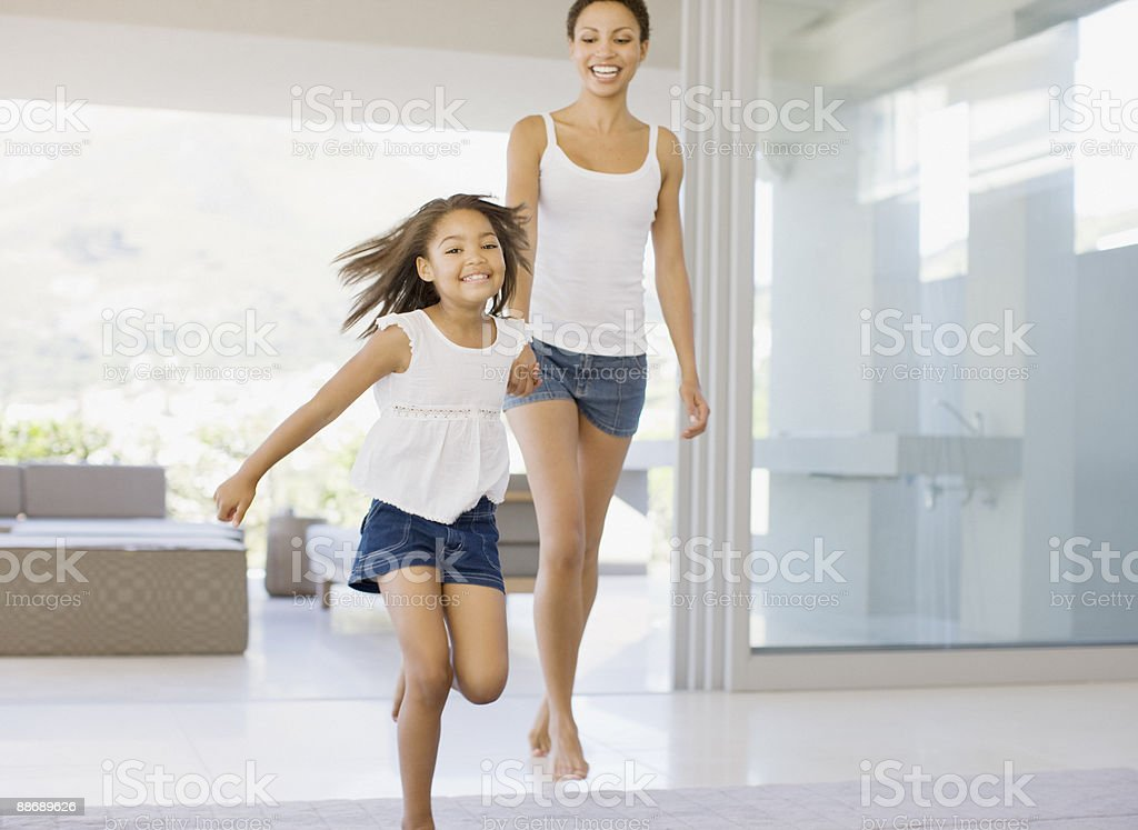 Mother and daughter holding hands and running stock photo