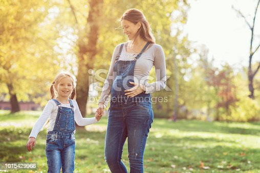 Happy smiling family of pregnant mother and her daughter on a sunny early autumn day