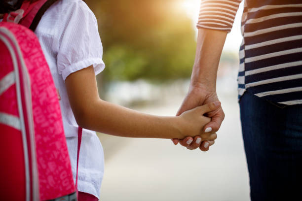 Mother and daughter holding hands stock photo