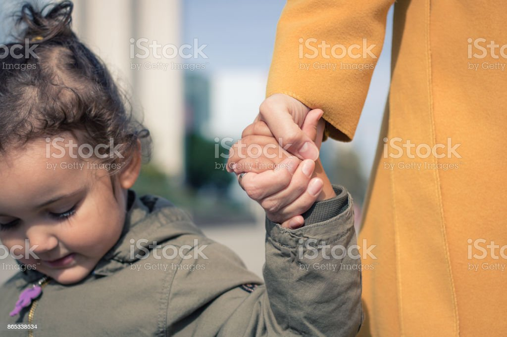 Mother and daughter holding hands. stock photo