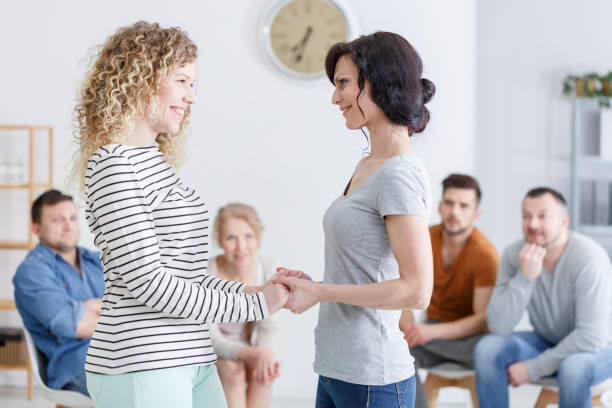 Mother and daughter holding hands Happy mother and daughter standing and holding hands in family counseling in a bright psychologist office drug rehab stock pictures, royalty-free photos & images
