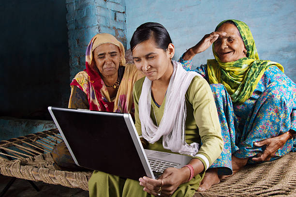 Mother and Daughter Holding Laptop at Home Village Women Working on Laptop with her Younger Daughter and Sitting on Charpai. The Shot is Taken using Studio Lights developing countries stock pictures, royalty-free photos & images