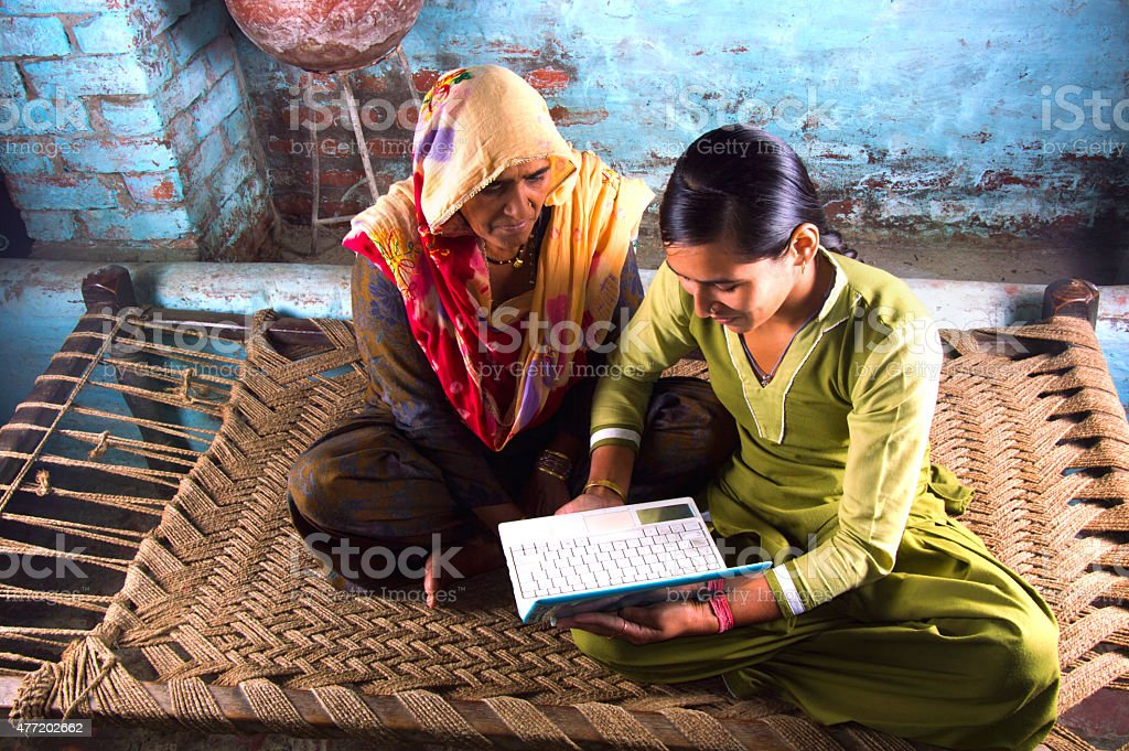 Mother and Daughter Holding Laptop at Home stock photo