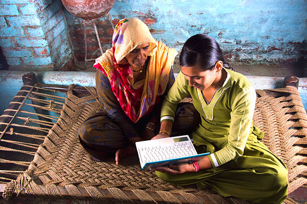 mother and daughter holding laptop at home - village stock pictures, royalty-free photos & images