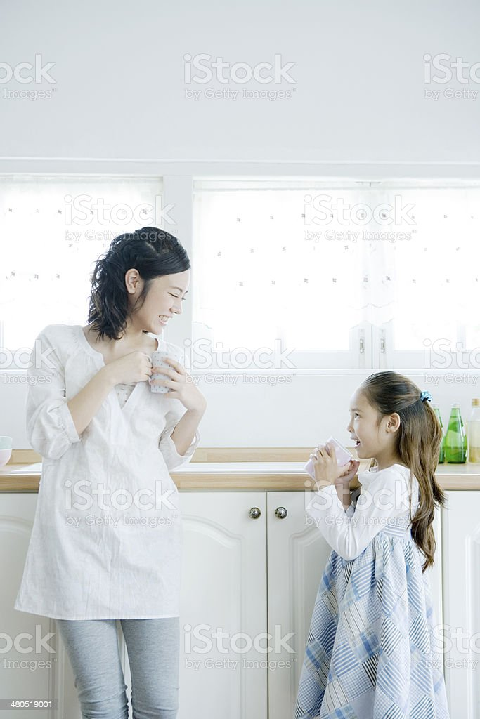 Mother and daughter holding mug in hand stock photo