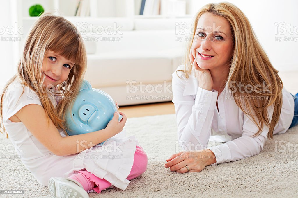 Mother and daughter holding piggybank royalty-free stock photo