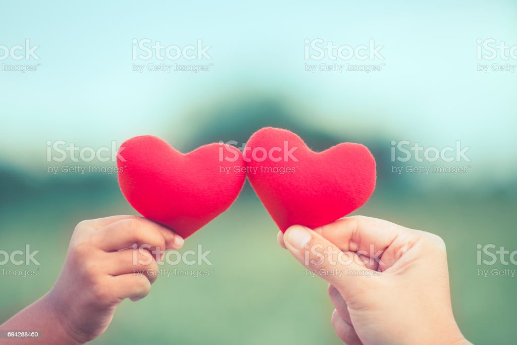 Mother and daughter holding red heart together in nature background - foto stock