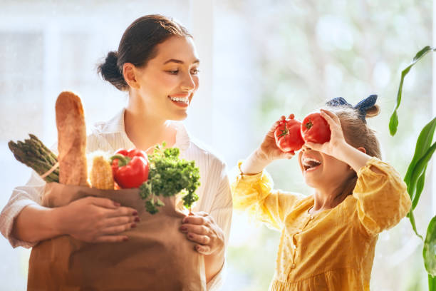 mother and daughter holding shopping bag - grocery home foto e immagini stock