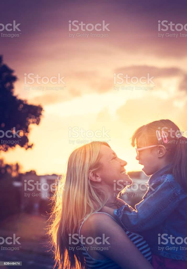 Mother and daughter hugging outdoors at sunset stock photo