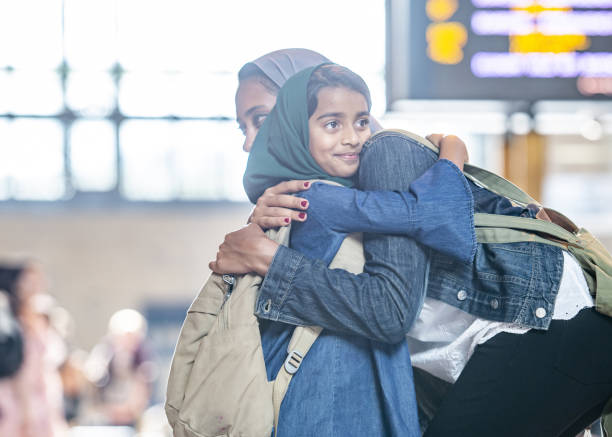 Mother And Daughter Hugging A Muslim mother and daughter are hugging at a bug station. immigrant stock pictures, royalty-free photos & images