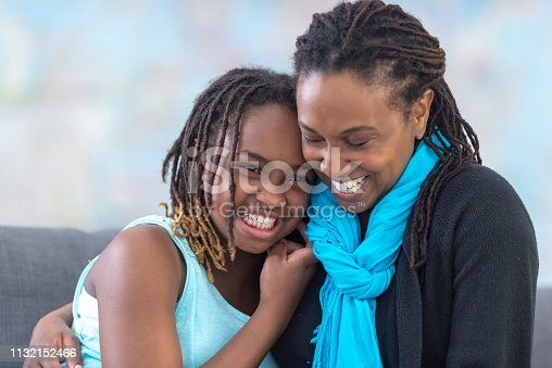 A beautiful mother of african descent smiles as she hugs her daughter. Her daughter is also smiling as she returns the affectionate embrace.