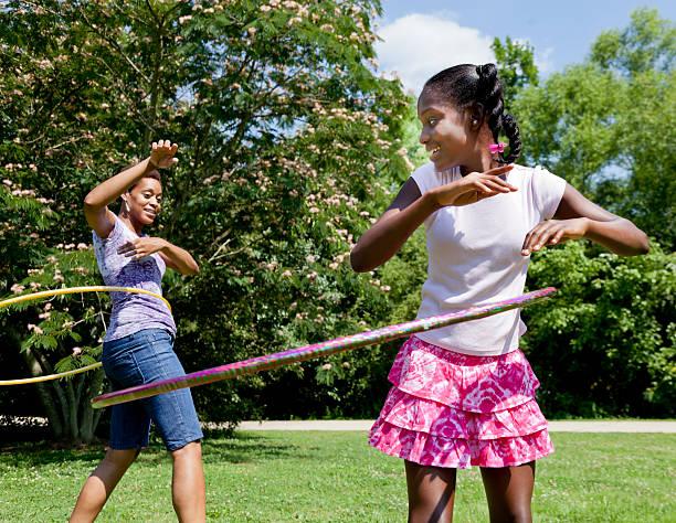 mutter und tochter beim hula-hoop - hula hoop workout stock-fotos und bilder