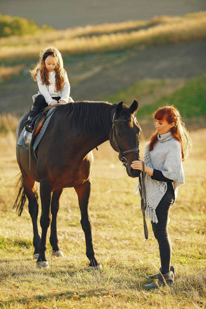Mother and daughter in a field playing with a horse stock photo