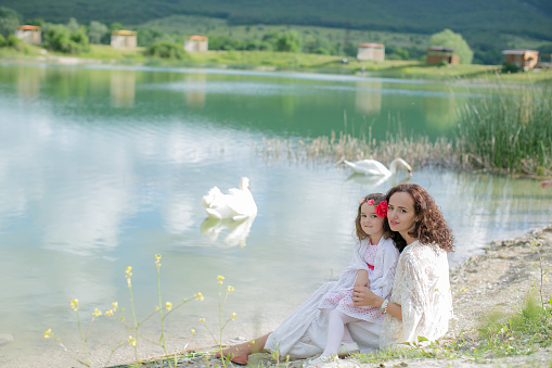 674214372 istock photo Mother and daughter in a meadow near a mountain lake 1210134940