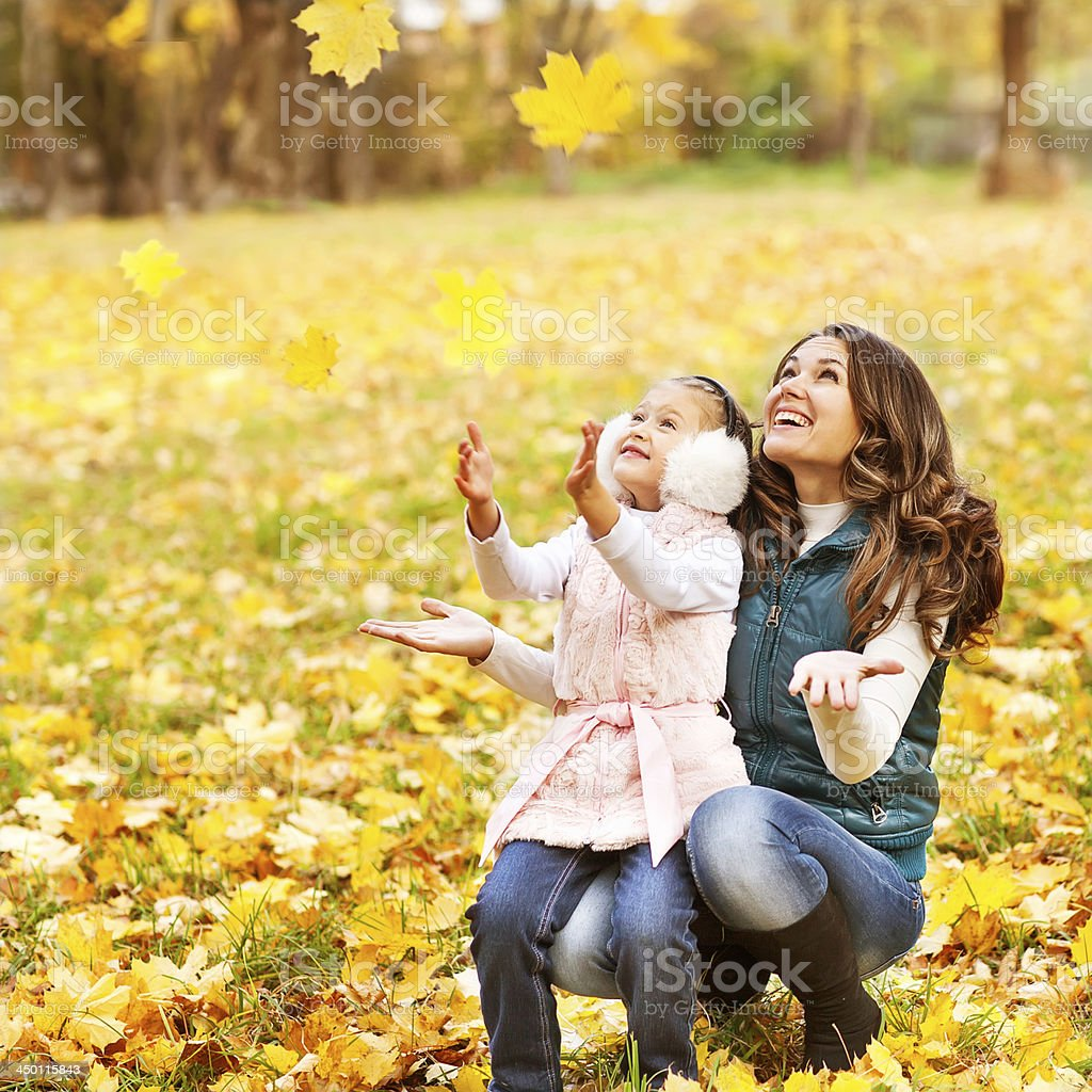 A mother and daughter in a park in the autumn months royalty-free stock photo