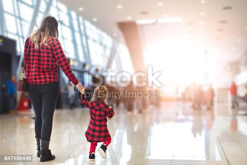 mom and her little girl walking in an airport hall