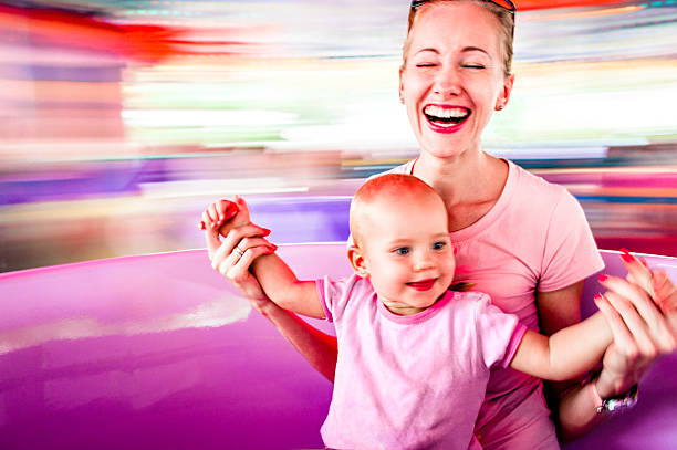mother and daughter in amusement park - school fete stock photos and pictures