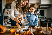 istock Mother and daughter in kitchen dusting cake with powdered sugar 1288141053