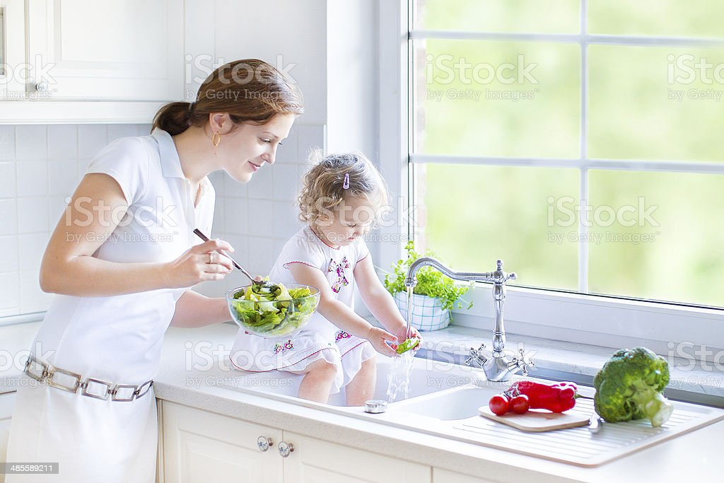 Mother and daughter in kitchen with big garden view window stock photo