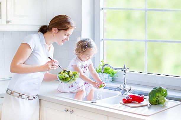 mutter und tochter in der küche mit großem fenster mit blick auf den garten - wasch oder spülbecken stock-fotos und bilder