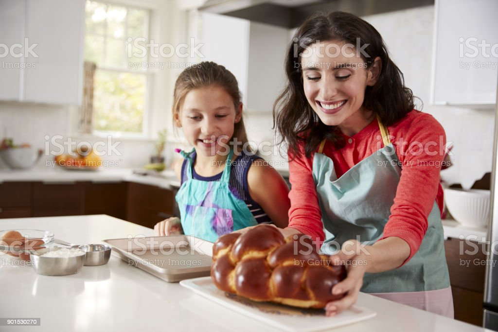 Mother and daughter in kitchen with freshly baked challah stock photo