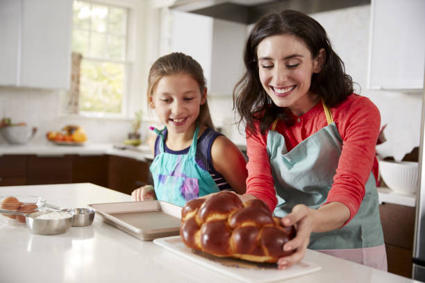 Mother and daughter in kitchen with freshly baked challah Mother and daughter in kitchen with freshly baked challah judaism stock pictures, royalty-free photos & images