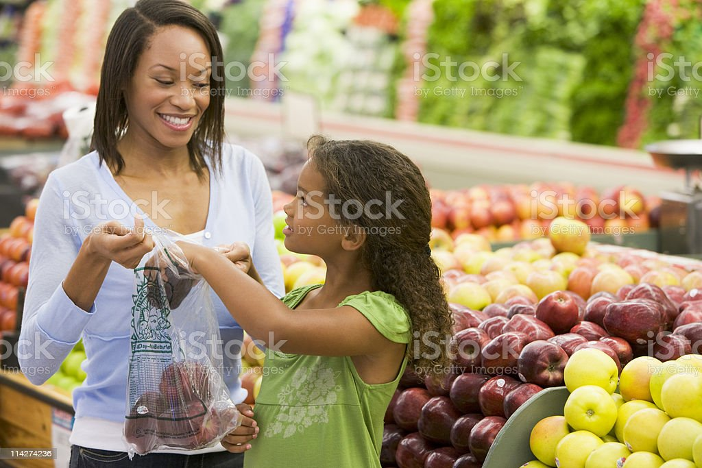 Mother and daughter in produce section stock photo