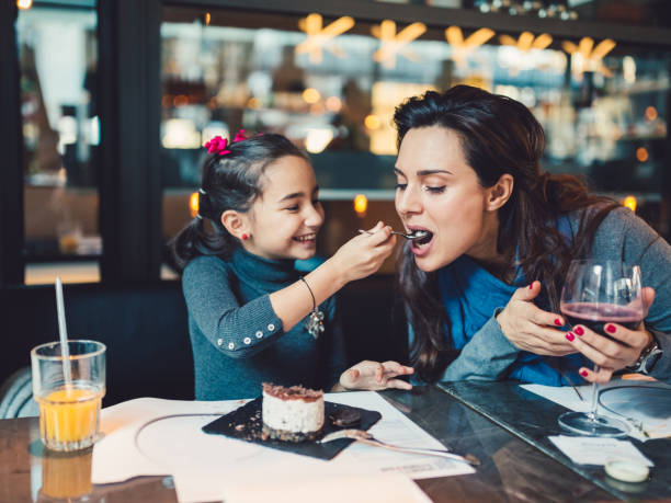 mother and daughter in restaurant - family dinner stock photos and pictures