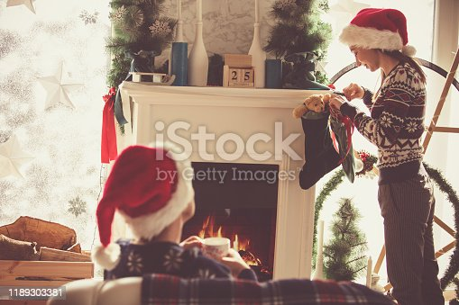 Shot of young woman, who is wearing Santa's hat, handing Christmas stocking on a fireplace, while her mother, who is also wearing Santa's hat is relaxing on the sofa and enjoying a cup of tea.