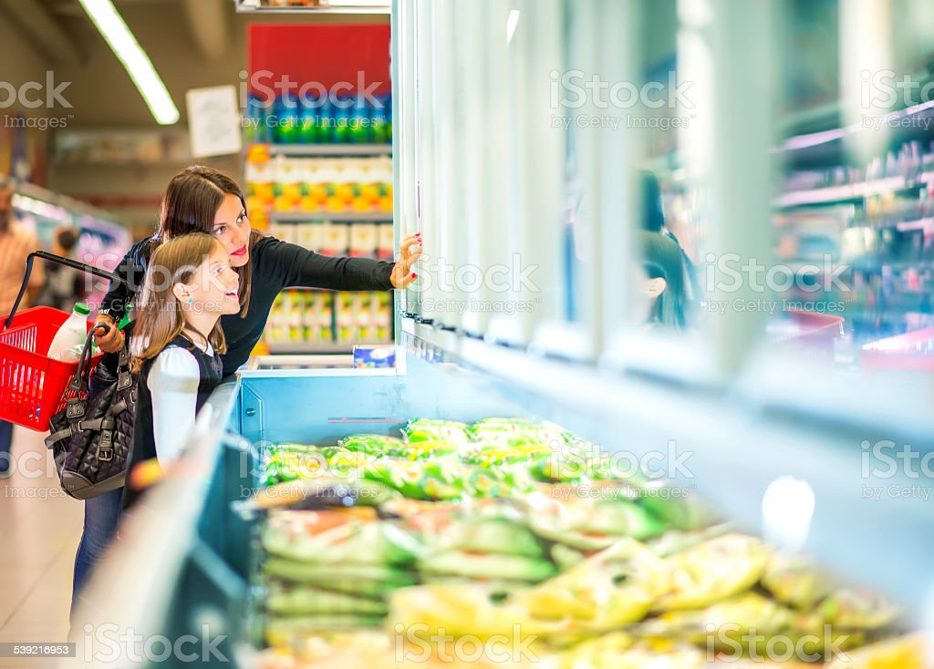 Mother and daughter in supermarket near frozen food stock photo
