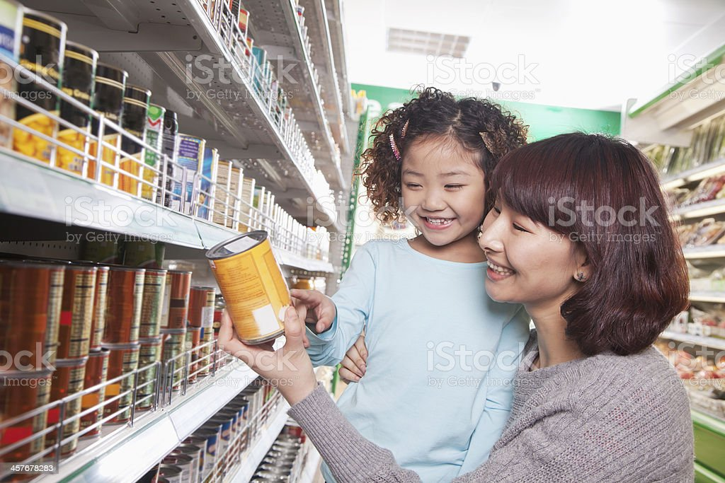 Mother and Daughter in Supermarket Shopping, Looking at a Product stock photo