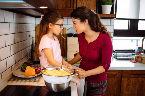 Mother and daughter in the kitchen, eating spaghetti together stock photo