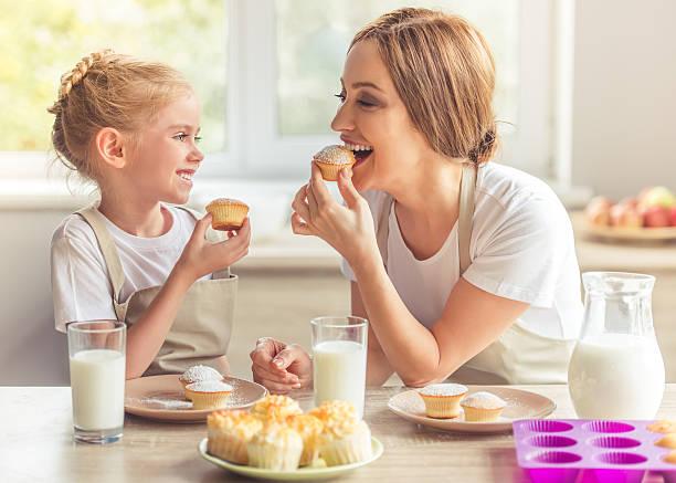madre e hija en la cocina - magdalena dulces fotografías e imágenes de stock