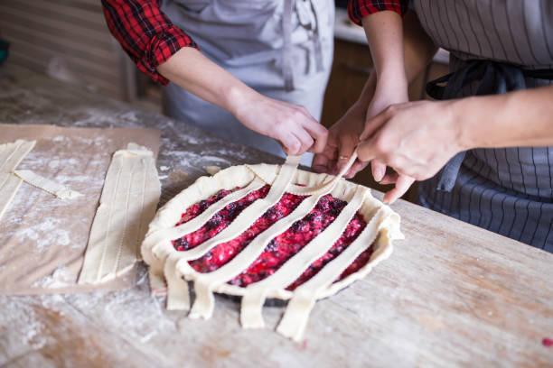 Madre e hija en la cocina preparando pastel de cereza - foto de stock