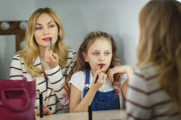 Mutter und Tochter im Spiegel malen Sie ihre Lippen. Reflexion – Foto