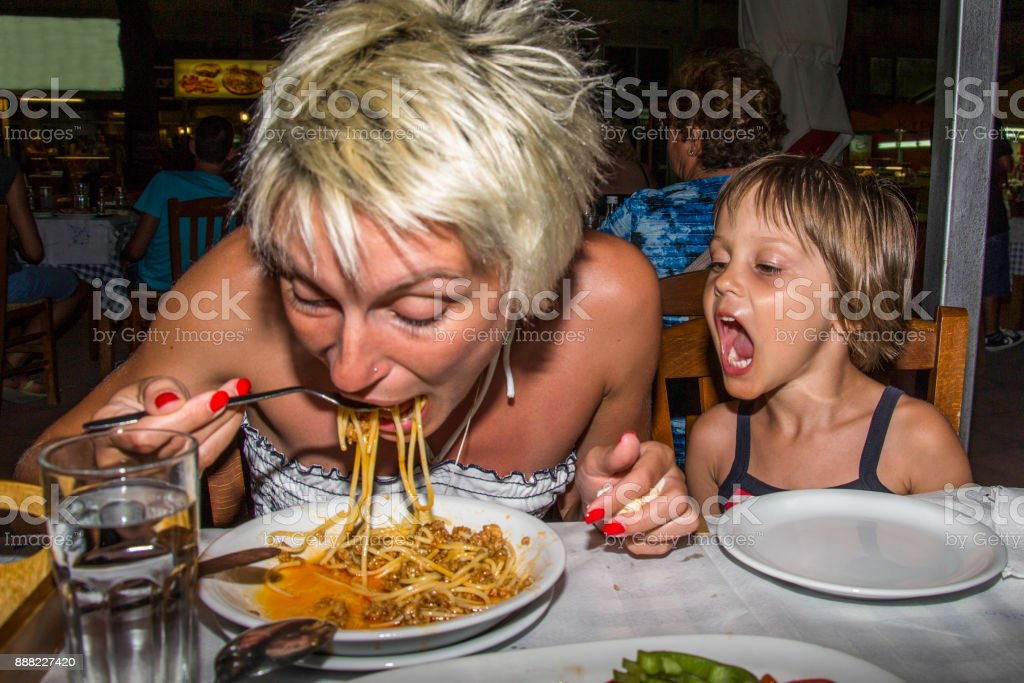 Mother and daughter in the restaurant eat spaghetti stock photo