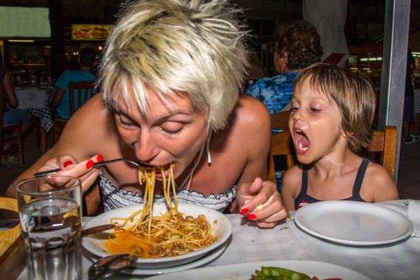 mutter und tochter im restaurant essen spaghetti - griechische partyspeisen stock-fotos und bilder