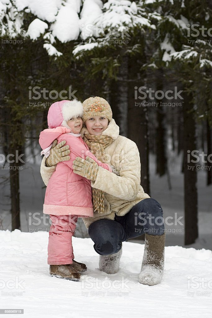 Mother and daughter in winter forest. royalty-free stock photo
