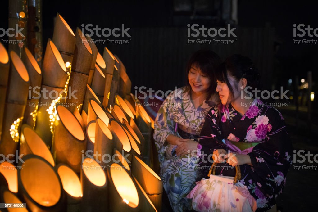 Mother and daughter in yukata looking at bamboo candle lights stock photo