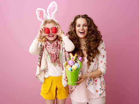 Pink Mood. happy stylish mother and daughter with wavy hair isolated on pink with handmade Easter eggs