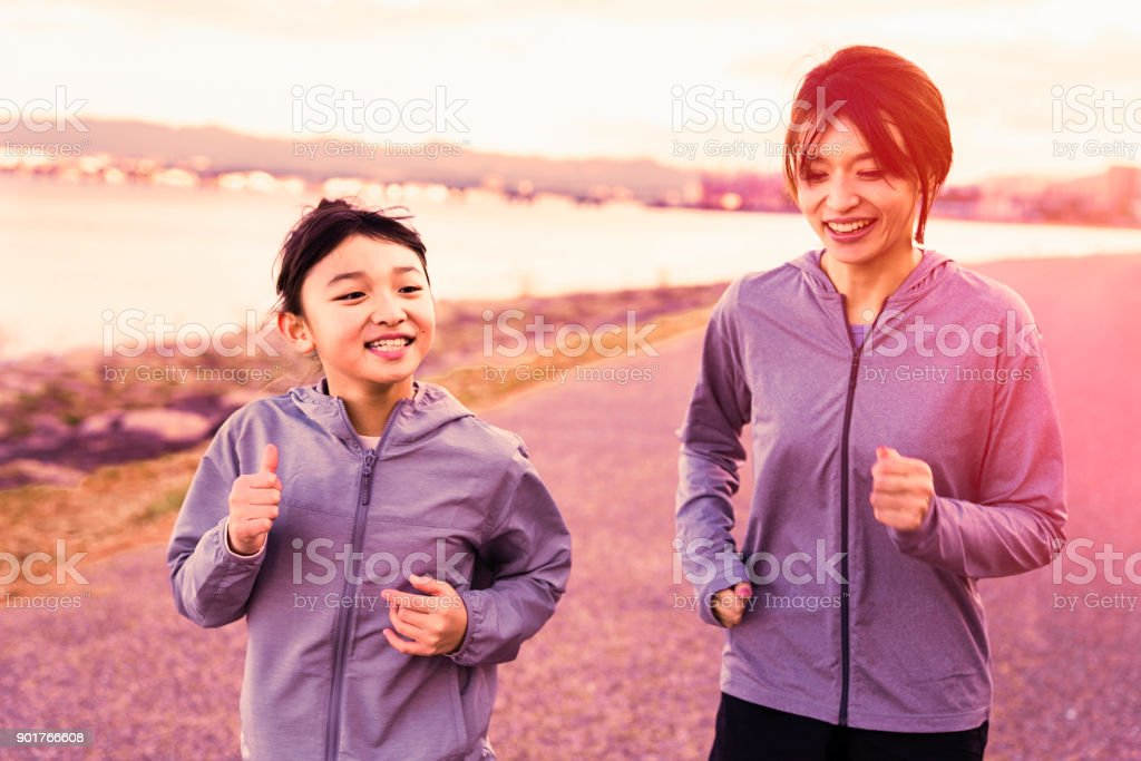Mother and daughter jogging outdoors in winter holidays stock photo