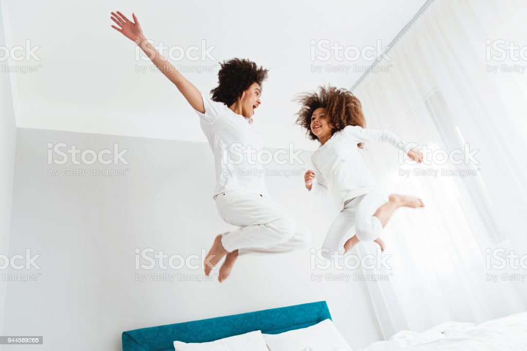 Mother and daughter jumping on the bed, happiness, joyful stock photo
