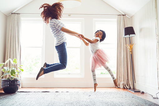 Side view of mother and daughter jumping while performing ballet. Woman and girl are practicing at home. Determined family is dancing against windows.
