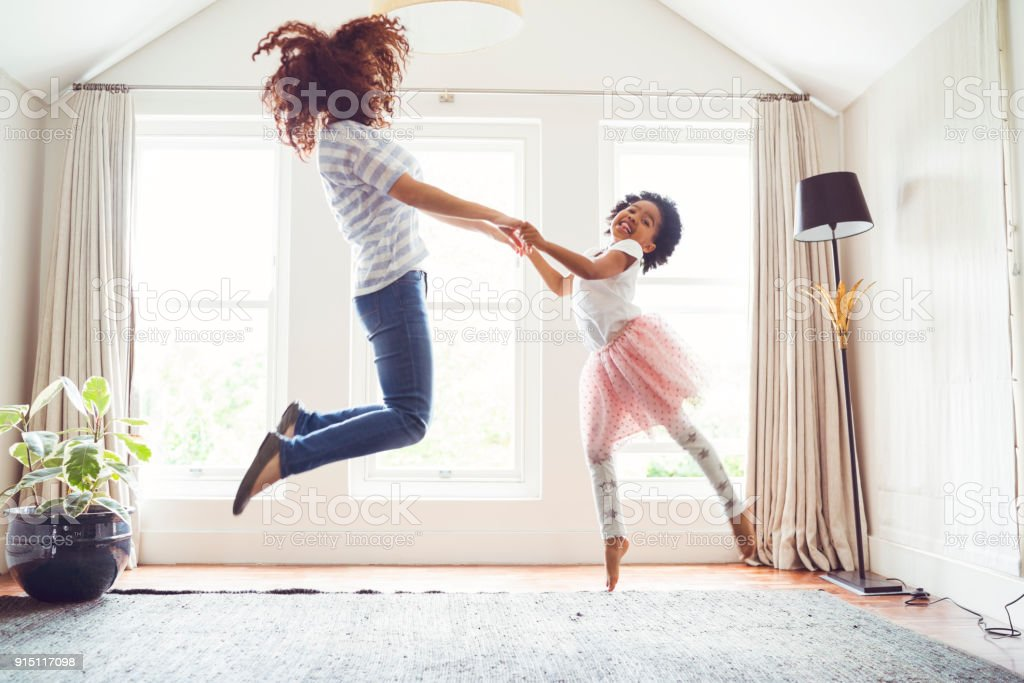 Mother and daughter jumping while doing ballet stock photo