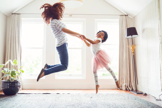 mother and daughter jumping while doing ballet - vitality stock photos and pictures