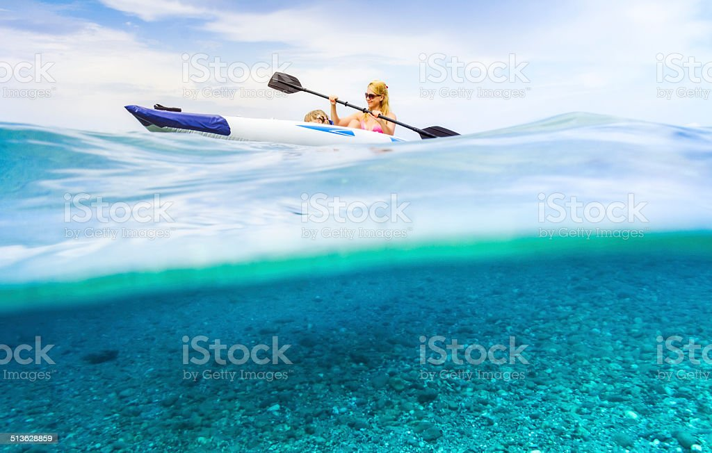 Mother and daughter kayaking on the Aegean Sea waves. stock photo